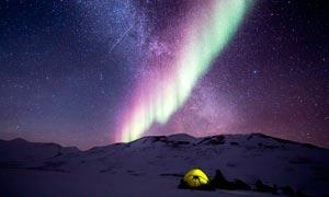 雪山頂上美麗的極光攝影圖片