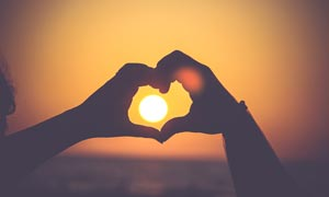 透过心形手势看日落高清摄影图片