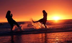 夕阳下在海边戏水的美女摄影图片