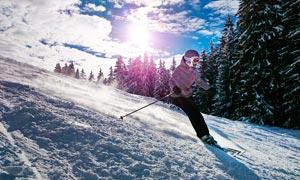 陽光下在雪山滑雪的女孩攝影圖片
