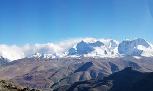 藍天下的雪山山巒攝影圖片
