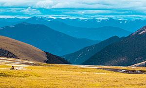 连绵的山川和山顶草地摄影图片