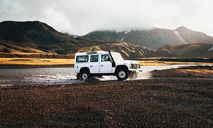 山腳下馳騁的白色越野車攝影圖片