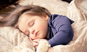 在床上熟睡的可愛女孩攝影圖片