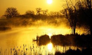 夕阳下雾气腾腾的湖泊摄影图片