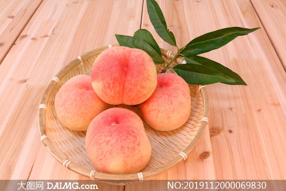 桌子上果盘里装着的桃子摄影图片