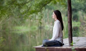 在湖边做瑜伽的女子摄影图片