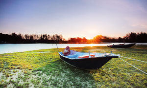 清晨湖邊放著的小舟攝影圖片