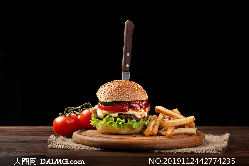 西红柿与刀插汉堡包等摄影高清图片