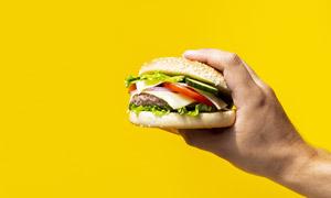 单手拿着的汉堡包特写摄影高清图片