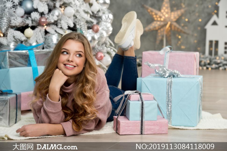 礼物盒与手抵着下巴的美女高清图片