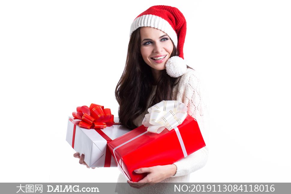 一手拿一个礼物的圣诞美女高清图片