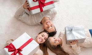 拿礼物盒躺地上的三口之家高清图片