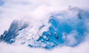 云雾缭绕的雪山景观摄影图片