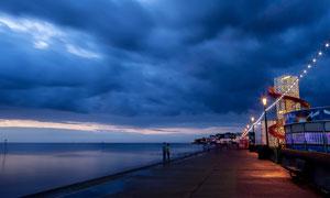 乌云下的海边夜景风光摄影图片