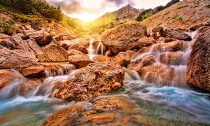 夕阳下岩石中的小溪流水摄影图片