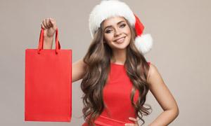 拎着手提袋的圣诞美女人物摄影图片