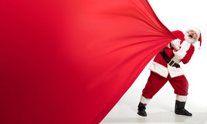 用力拉紅布的圣誕老人創意高清圖片