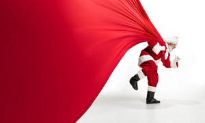 奋力往前拉红布的圣诞老人高清图片
