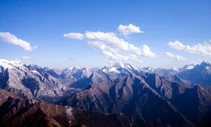 藍天白云下的連綿山峰高清攝影圖片