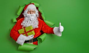 破洞而出送礼物的圣诞老人高清图片