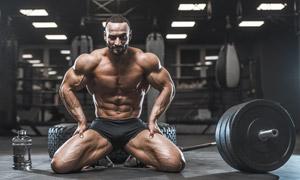 在杠铃旁边展示肌肉的男子高清图片
