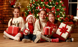 抱著禮物坐地板上的孩子們高清圖片