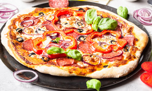 洋蔥圈與辣椒圈點綴的披薩高清圖片