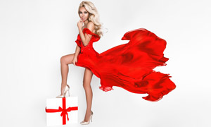 腳踩著禮物的紅裙美女攝影高清圖片