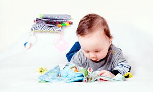 趴在床上撫摸玩具的嬰兒攝影圖片