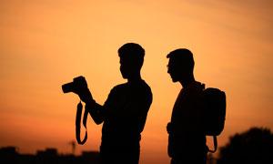 黄昏下手拿相机的人物剪影摄影图片