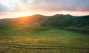 夕阳下的草原和山丘高清摄影图片