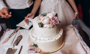在桌上花朵装饰的婚庆蛋糕摄影图片