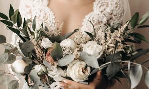 懷里抱著一束花的新娘特寫高清圖片