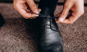 蹲下來系鞋帶場景特寫攝影高清圖片