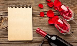 记事本与花瓣酒杯酒瓶摄影高清图片