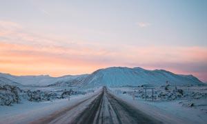 傍晚雪山上的公路美景摄影图片