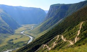山坡上的山路和峡谷下的河流摄影图片