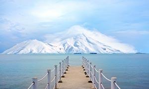 雪山下的海洋和海边栈桥摄影图片