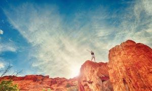 站在悬崖上双手高举的女人摄影图片
