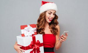 抱着礼物看手机的美女摄影高清图片