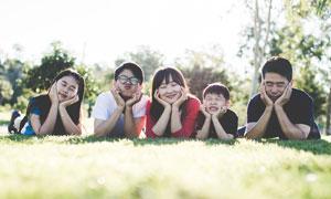 一家人瞇著眼睛趴在草地上攝影圖片