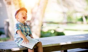 坐在板凳上大笑的男孩攝影圖片