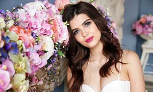 頭靠在花墻上的卷發美女攝影圖片