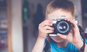 拿着相机正在拍摄的小男孩摄影图片
