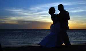 海邊黃昏下擁抱的情侶剪影攝影圖片