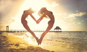 沙灘上兩個跳起的女子擺出心形攝影圖片