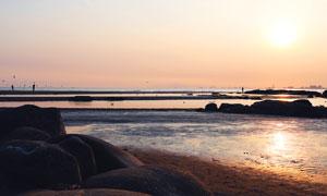 夕陽下的海灘和原石高清攝影圖片