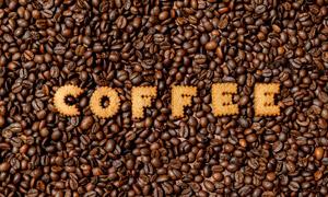在一堆咖啡豆上的字母饼干高清图片