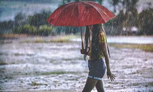 撑着伞走在雨中的长发美女摄影图片